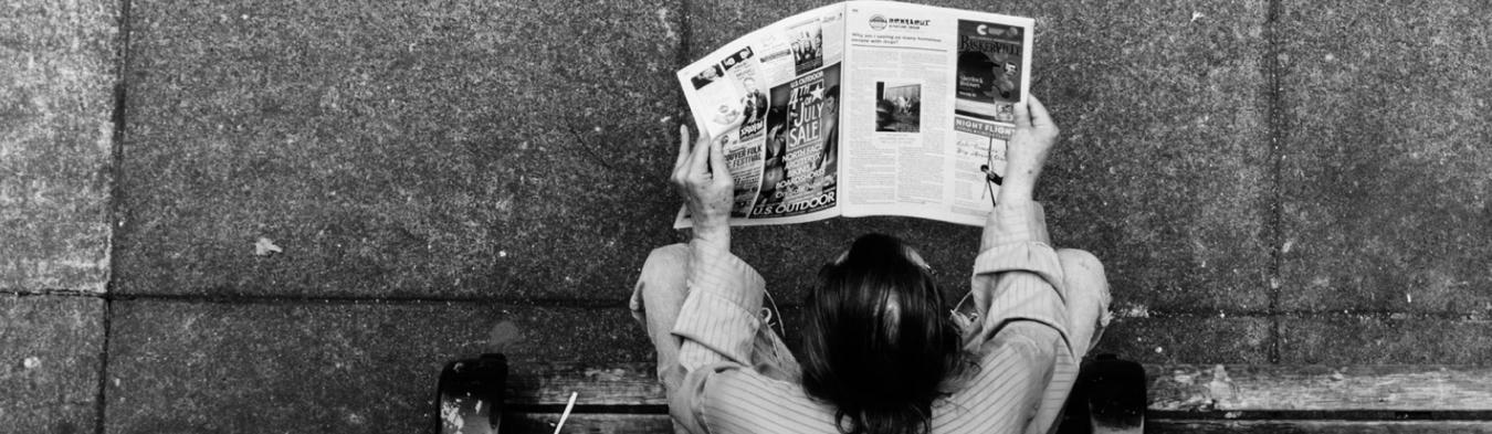 A black and white image of a person reading a newspaper